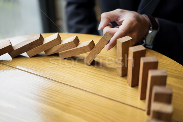 businessman hand stop dominoes continuous toppled or risk with c Stock photo © snowing