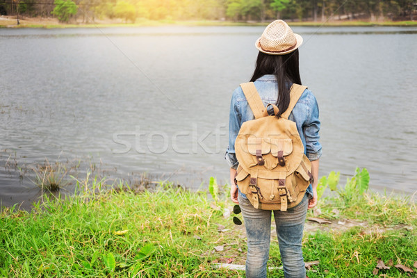 Confident woman posing on the shore of a wild lake, with mountai Stock photo © snowing