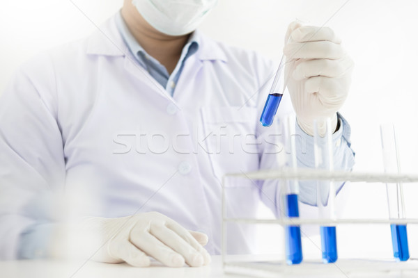 Asian scientific researcher working in laboratory holds test tub Stock photo © snowing