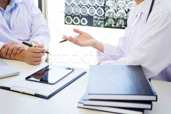Two doctors analyzing a scan or x-ray film or  explains a CT sca Stock photo © snowing