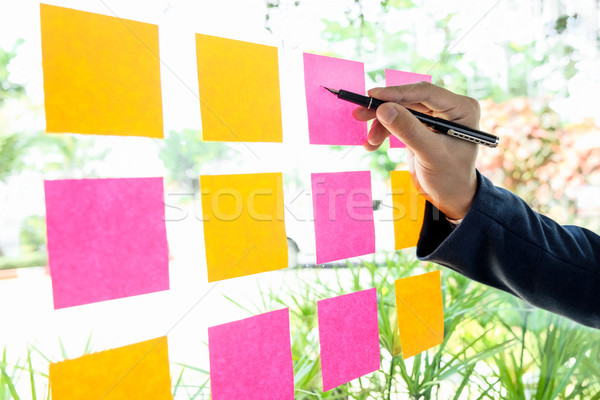 Close up shot of hands of woman sticking adhesive notes on glass Stock photo © snowing