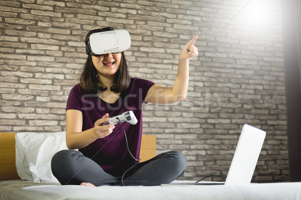 Happy smiling young woman playing game while getting experience  Stock photo © snowing