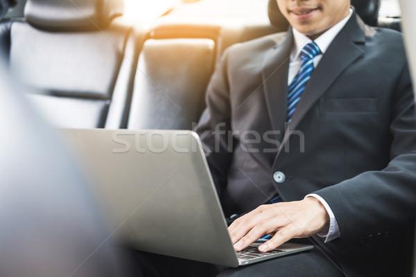 Bello giovani imprenditore utilizzando il computer portatile seduta indietro Foto d'archivio © snowing