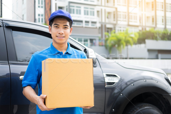 Delivery messenger man with cardboard box  outside the warehouse Stock photo © snowing