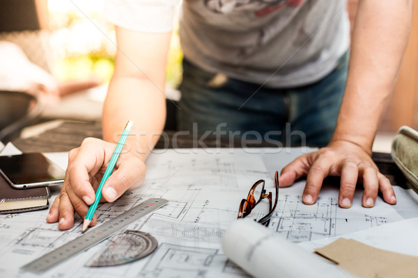 Stock photo: Close-up Of Person's Hand Drawing Plan On Blue Print with archit