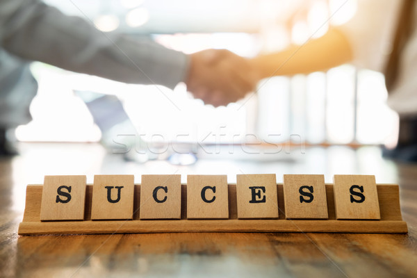 success word on wood table with business man shaking hands durin Stock photo © snowing