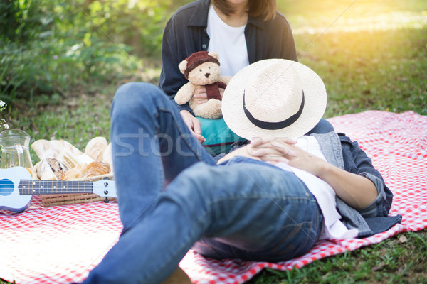 Casual handsome man put his head on knees his wife during picnic Stock photo © snowing