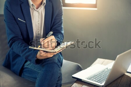 Thoughtful young business man in casual shirt holding note pad   Stock photo © snowing