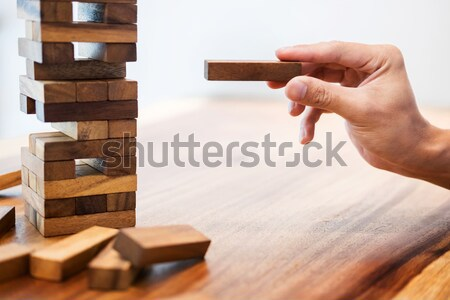 Business man placing wooden block on a tower concept of risk con Stock photo © snowing