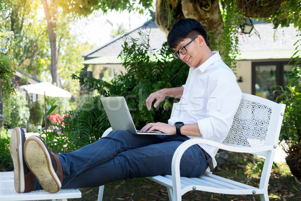 Stock photo: Young business man sitting on the park bench with laptop on his