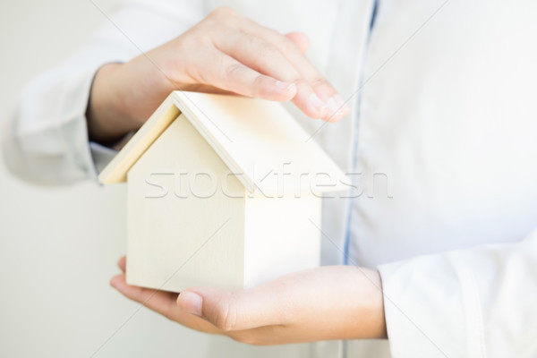 Stock photo: Female hands saving small house, Real estate business. insurance