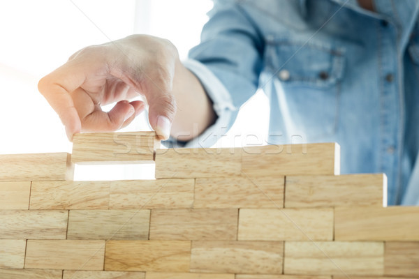 Hand of engineer playing a blocks wood tower game (jenga) on blu Stock photo © snowing