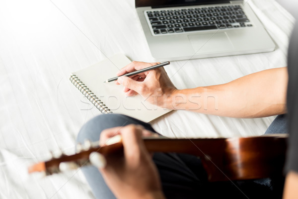Happy young asian man playing ukulele sitting on bed in bedroom. Stock photo © snowing
