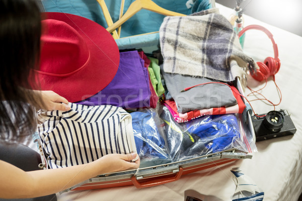 Woman hand packing a luggage for a new journey and travel for a  Stock photo © snowing