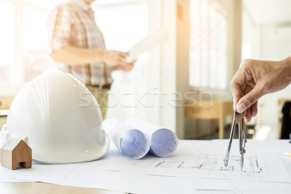 Close-up Of Person's Hand Drawing Plan On Blue Print with archit Stock photo © snowing