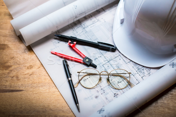 construction concept image helmet rolled blueprints on wooden bo Stock photo © snowing