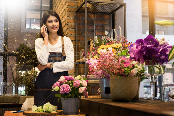 florist standing at her flower shop and using her telephone to t Stock photo © snowing