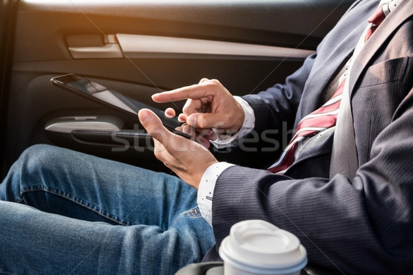 Stock photo: young handsome businessman working in back of car and using a ta