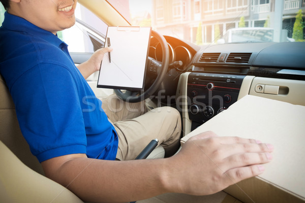 Delivery man with cardboard box checking document list In van an Stock photo © snowing