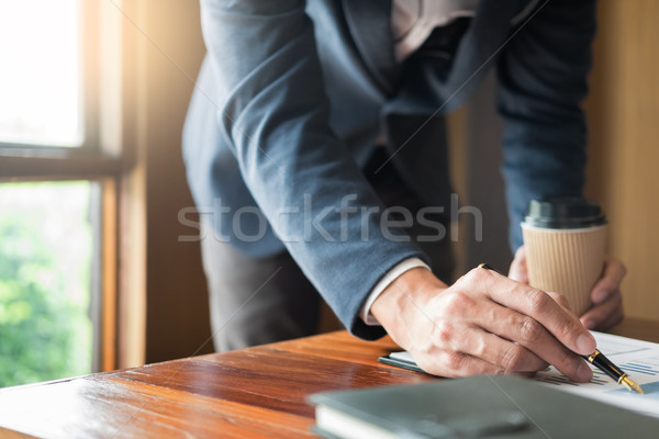 Casual businessman sitting at his desk online working in the of Stock photo © snowing