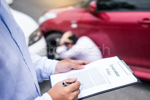 Insurance agent writing on clipboard while examining car after a Stock photo © snowing