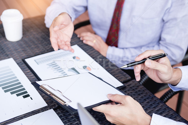 Business people discuss together about there work by graph docum Stock photo © snowing