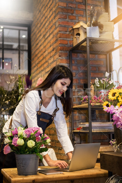 Women florist looking laptop got order at counter of her flower  Stock photo © snowing