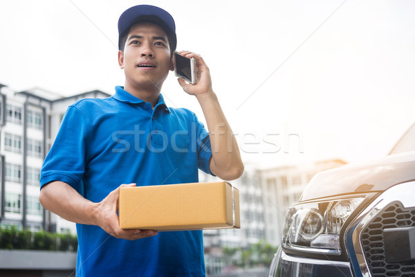 messenger man hold box and talk on smart phone and payment termi Stock photo © snowing