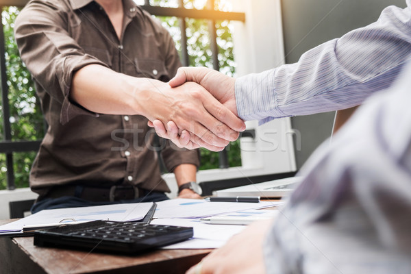 Two confident business man shaking hands during a meeting at out Stock photo © snowing
