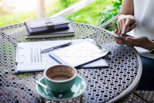 woman using smart phone and coffee beside on a wooden table in g Stock photo © snowing
