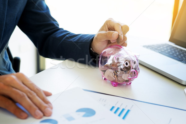 Close up of Businessman putting coin into small piggy bank , The Stock photo © snowing