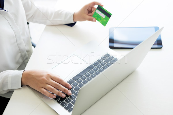 Stock photo: Closeup of happy young woman holding credit card inputting infor