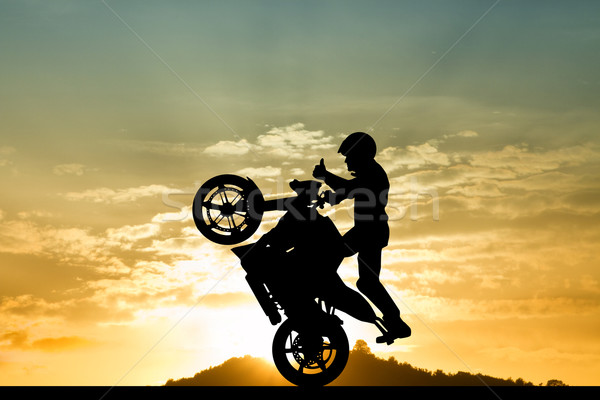 stuntman motorcyclist at sunset Stock photo © sognolucido