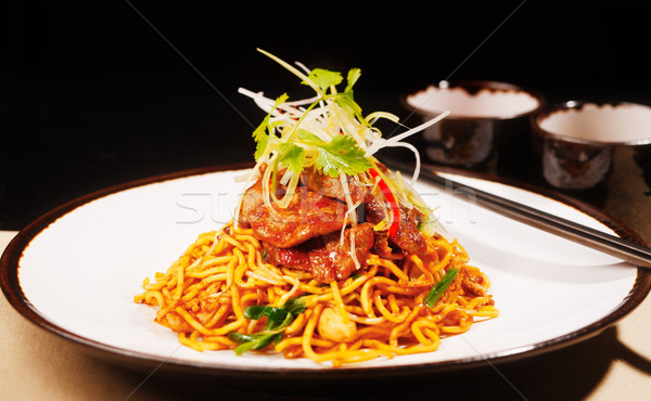 Wok fried Szechwan chicken on a bed of noodles Stock photo © SophieJames