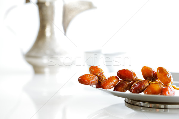 Arabic dates on a plate with Arabic coffee pot of the Bedouin Stock photo © SophieJames