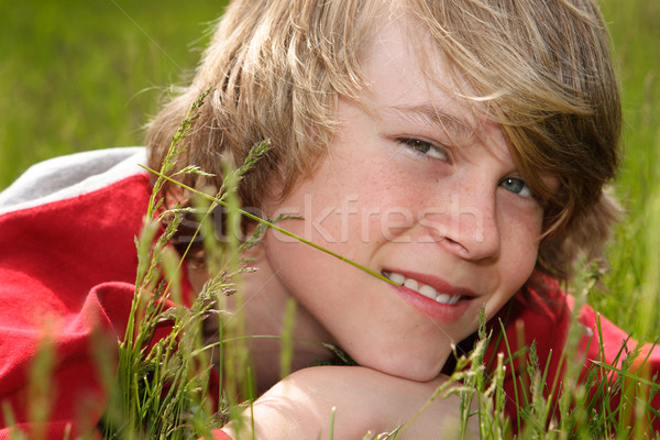 Teenage boy laying in a field of grasses Stock photo © soupstock