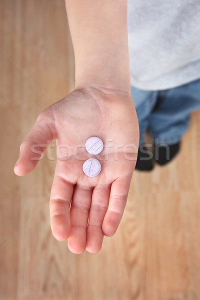 child's hand holding medicine tablets Stock photo © soupstock