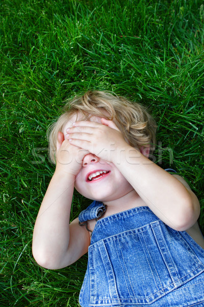 Laughing boy covering his eyes Stock photo © soupstock