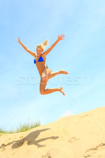 Girl jumping off a sand dune Stock photo © soupstock