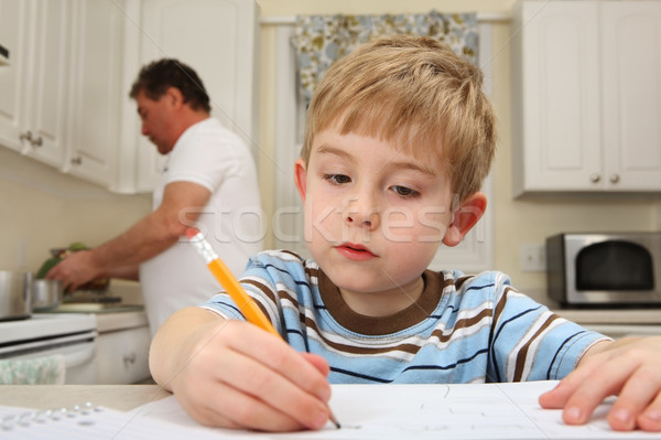 Young boy drawing while father works in kitchen Stock photo © soupstock