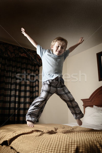 Young boy jumping on the bed Stock photo © soupstock