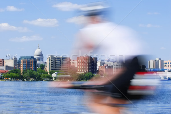 Motion blur of a person riding a bicycle past the capitol of Wis Stock photo © soupstock