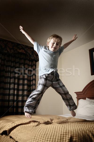 Fiatal srác ugrik ágy gyermek jókedv fiú Stock fotó © soupstock