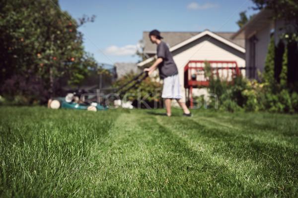 Teenage boy mowing lawn Stock photo © soupstock