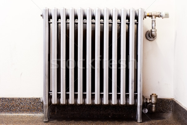 Stock photo: Closeup of an old radiator with a new thermostat