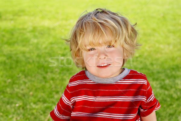 Sorridere ragazzo seduta fuori Foto d'archivio © soupstock