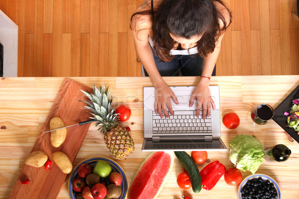 Woman using a Laptop while cooking Stock photo © Spectral