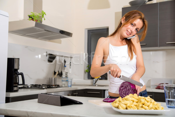 Redhead girl slicing in kitchen telephoning Stock photo © Spectral