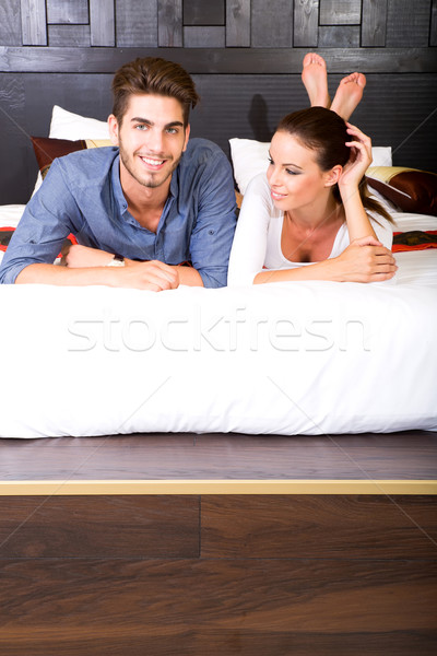 Stock photo: A young couple lying on the bed in an asian style hotel room