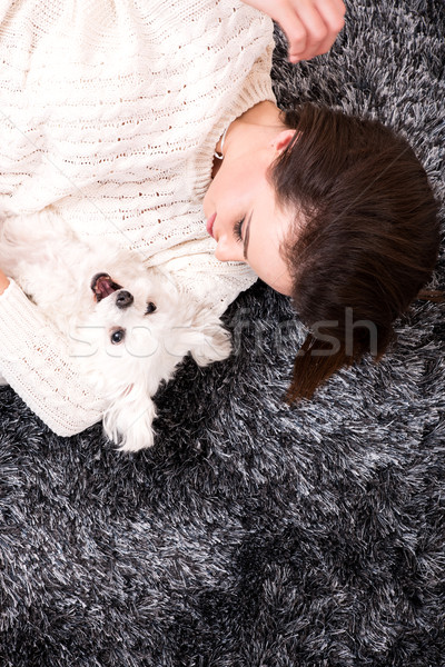 Young beautiful woman cuddling her Dog on the carpet	 Stock photo © Spectral